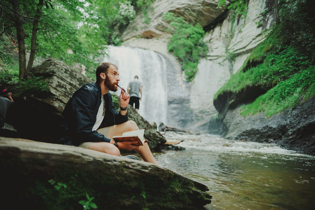 Man thinking on rock in front of waterfall